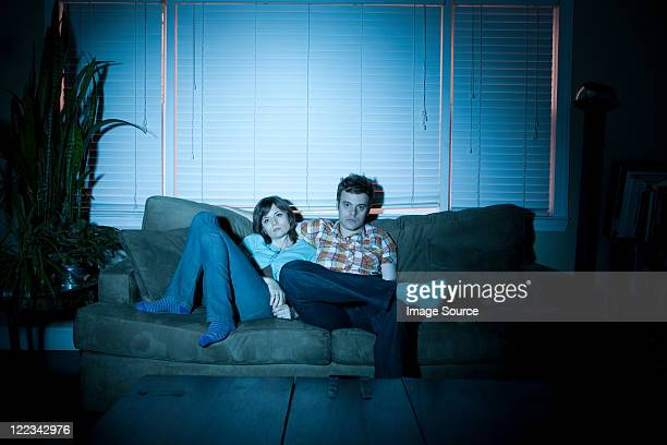Young couple watching tv, bored