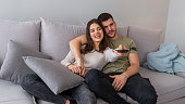 Young couple watching TV in evening at home. Happy young couple relaxing and watching TV at home. Couple watching tv on sofa in evening