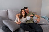 Portrait of a laughing young couple hugging while sitting together on a sofa at home and watching TV. Couple on sofa with TV remote. Happy young couple preparing to watch a movie at home.