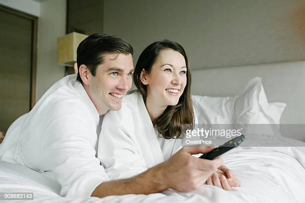 Pareja joven viendo televisión en habitación de Hotel