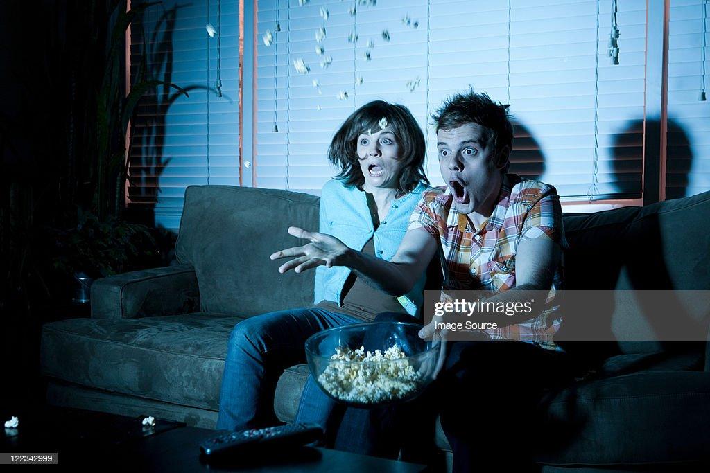 Young couple watching tv, man throwing popcorn