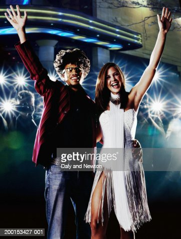 Young couple waving, smiling, crowd taking photos in background : Foto de stock