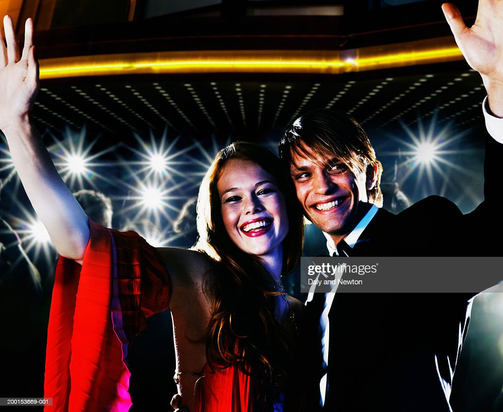 Young couple waving, smiling, crowd taking photos in background : Stock Photo