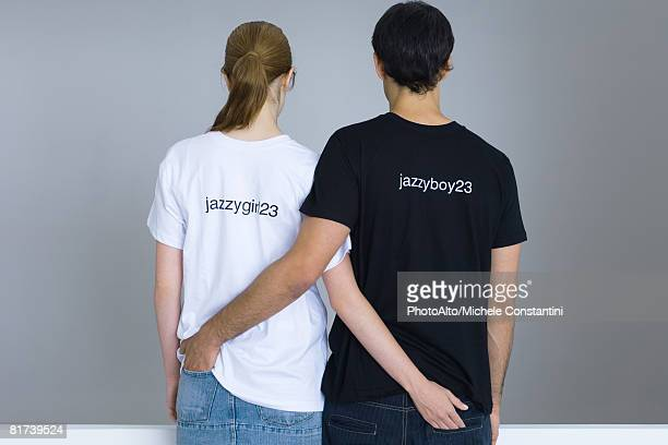 Young couple wearing customized tee-shirts, arms around each other's waists, rear view
