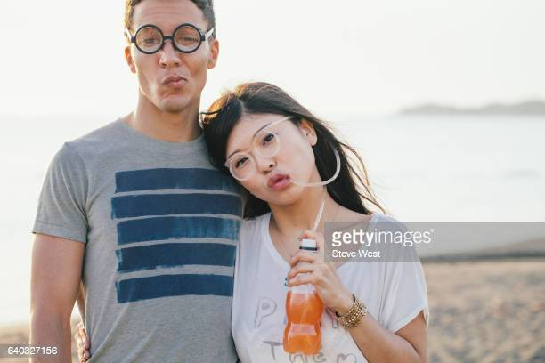 Young Couple Wearing Fun Glasses On The Beach