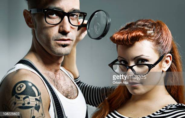 Young Couple Wearing Glasses and Holding Magnifying Glass