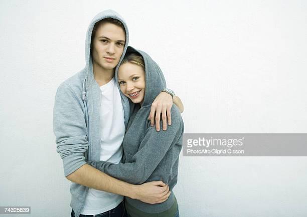 Young couple wearing hooded sweatshirts, embracing