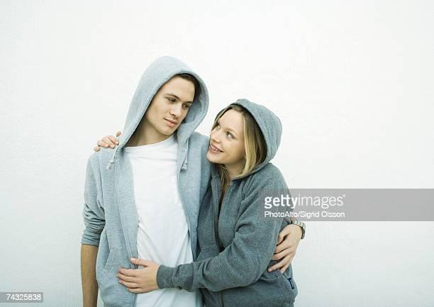 Young couple wearing hooded sweatshirts