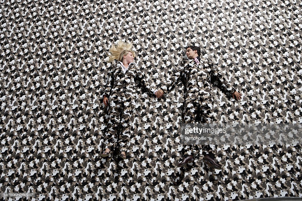 Young couple wearing patterned suits blending into background