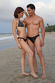 Young couple wearing swimwear and standing on the beach