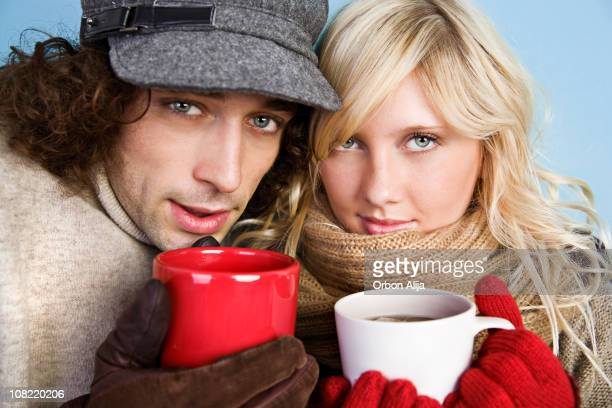 Young Couple Wearing Winter Clothes Holding Mugs of Coffee