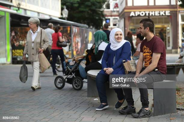 A young couple who said they are from Syria relax on a bench in the historic city center on August 25 2017 in Goslar Germany City authorities in...