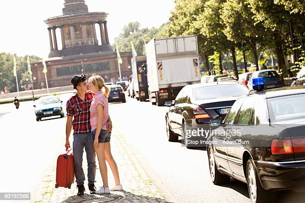 A young couple with a suitcase kissing