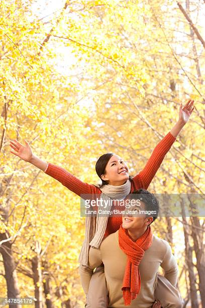 Young couple with arms outstretched, Autumn leaves in the background