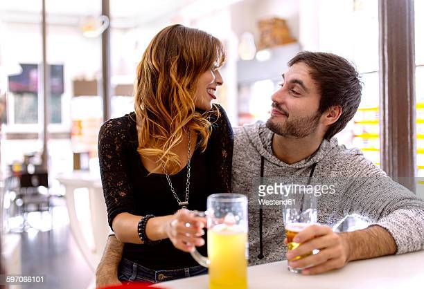 Young couple with beverages relaxing in a pub