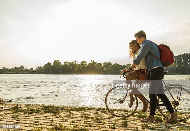 Young couple with bicycle by the riverside