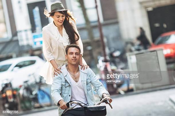 Jeune couple avec vélo à travers les rues de la ville