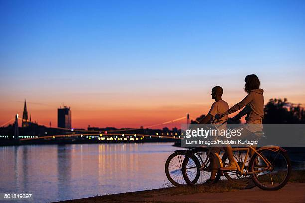 Young couple with bicycles at night, looking at city, Osijek, Croatia