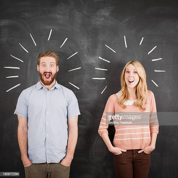 Young couple with blackboard in background, studio shot