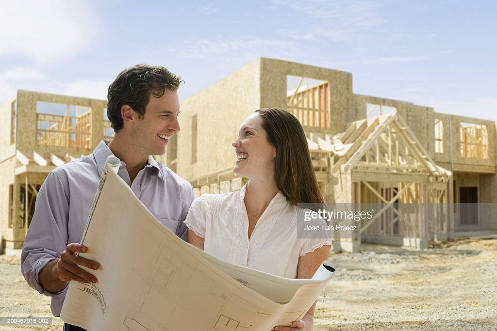 Young couple with blueprints at building site (Digital Composite) : Stock Photo