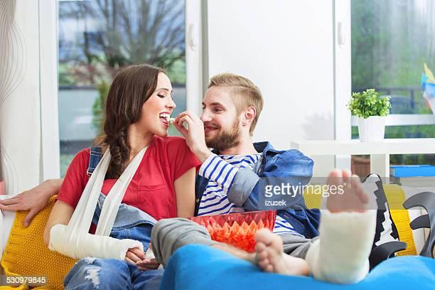 Pareja joven con los brazos pierna fracturada y comiendo palomitas de maíz