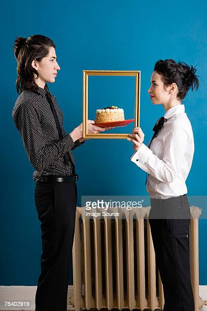 Young couple with cake and picture frame
