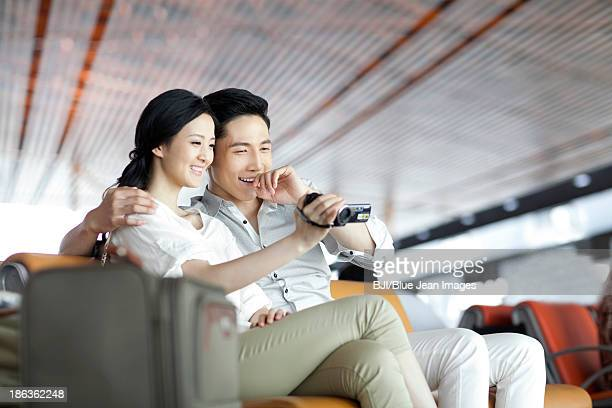 Young couple with camera in airport lounge