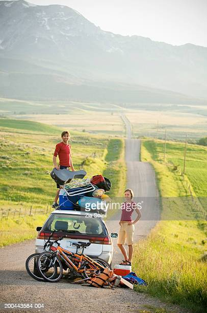 Young couple with car loaded with vacation gear