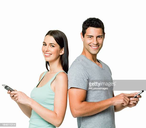 Young couple with cell phones on white background
