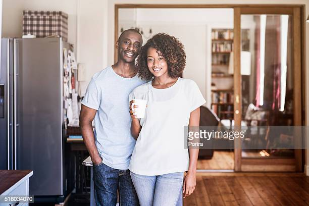 Young couple with coffee cup standing at home