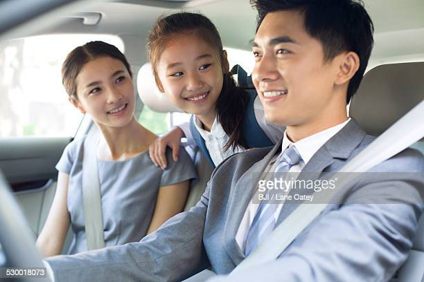 Young couple with daughter riding in car together