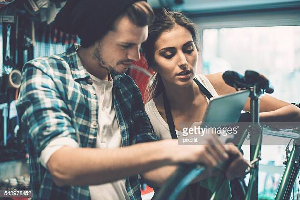 Young couple with digital tablet repairing a bike