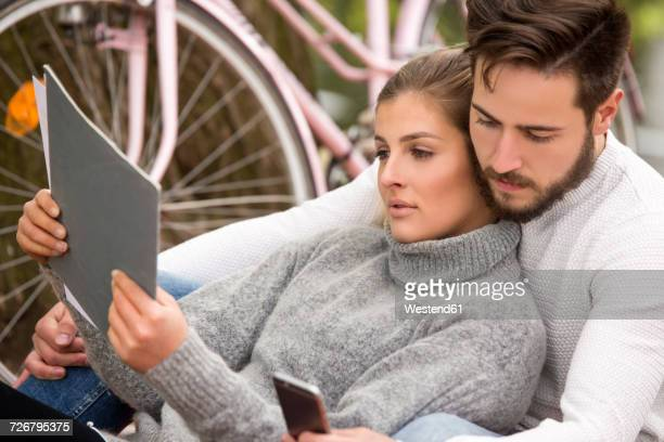Young couple with documents and cell phone