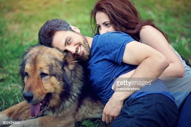 Unga par med hund kramas på gräset
