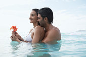 Young couple with flower hugging in water, St. John, US Virgin Islands, USA