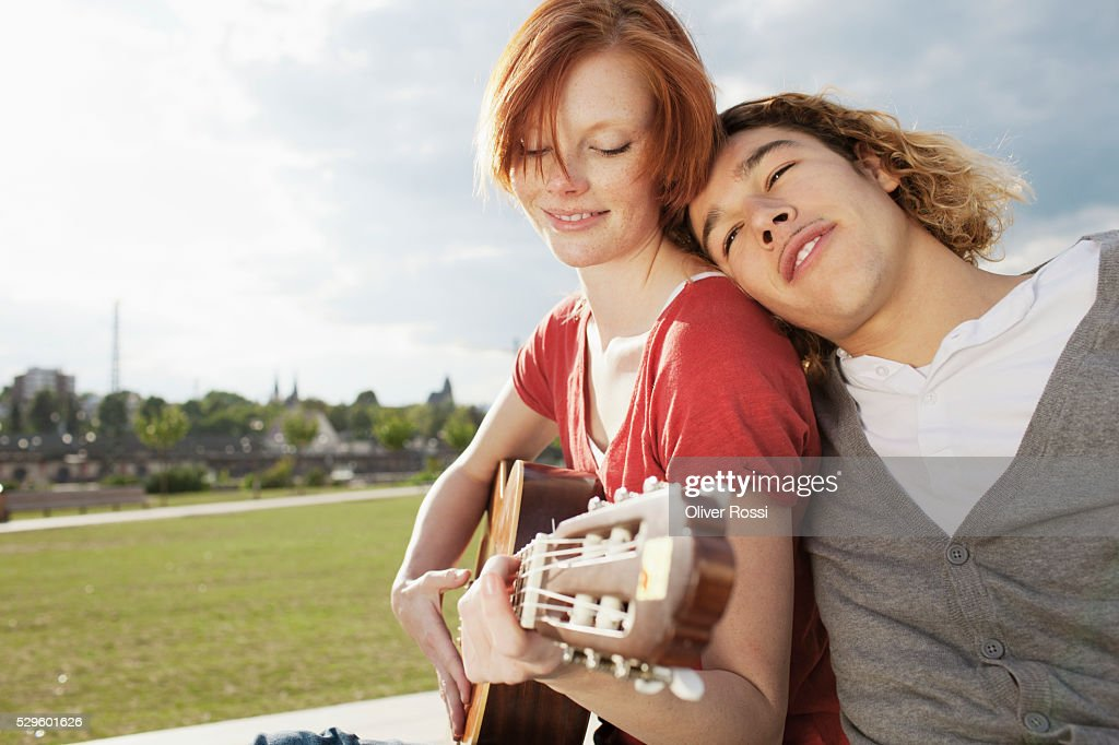 Young couple with guitar relaxing in park : Foto de stock
