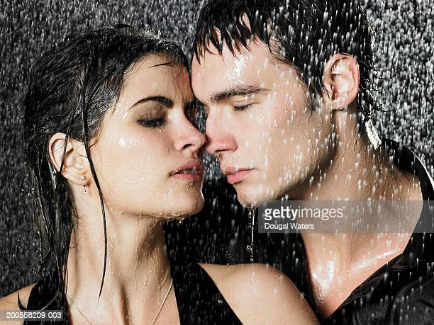 Young couple with heads together in rain at night