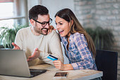 Young couple with Laptop Computer and Credit Card buying online.