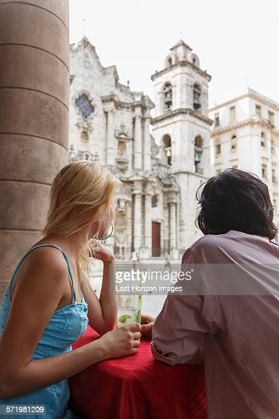 Young couple with Mojito cocktails in a restaurant on the Plaza de la Cathedral of Havana, Cuba