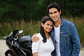 Young couple with motorbike smiling at camera