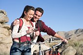 Young couple with mountain bikes stand looking at camera