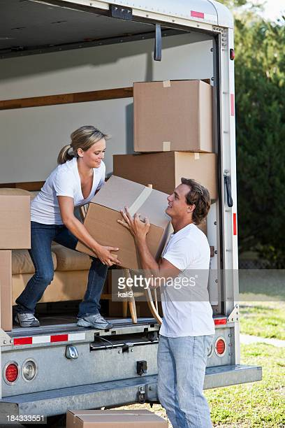 Young couple with moving van in driveway lifting boxes