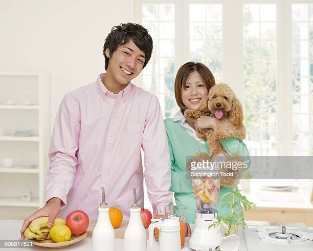 Young Couple With Pet Dog In Kitchen