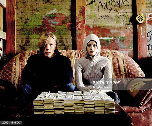 Young couple with pile of bank notes, portrait