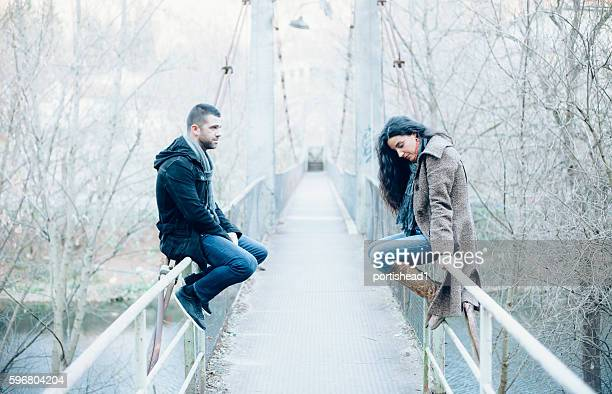 Young couple with relationship difficulties sitting on a bridge