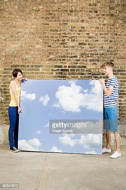 Junges Paar mit Himmel und Wolken im Hintergrund