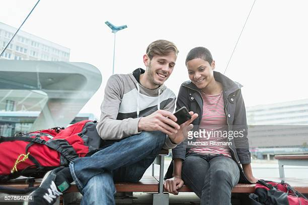 Young couple with smartphone at bus stop