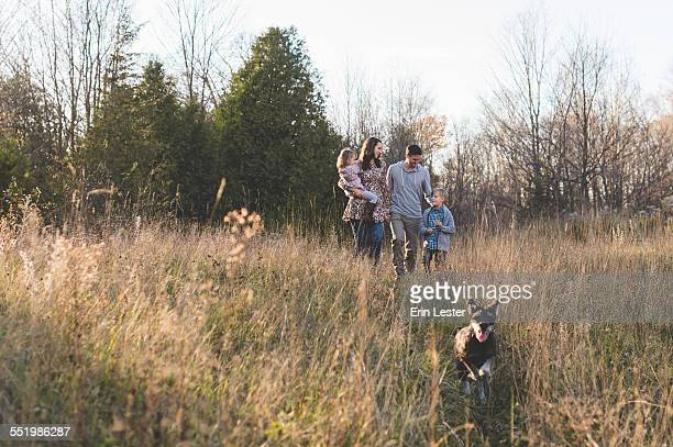 Young couple with son and daughter walking the dog