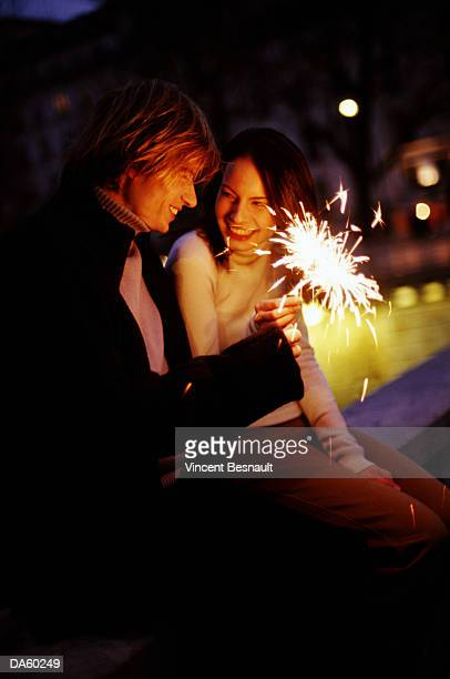 Young couple with sparklers outdoors at night
