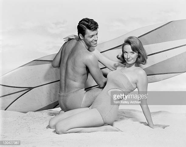 Young couple with surfboard on beach, smiling